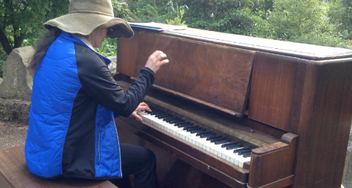 hand up playing brown console piano