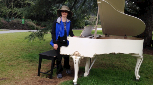 standing by white grand piano
